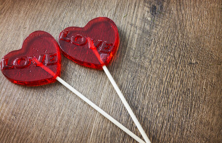 st  valentines day: red candies with heart shaped topping on wooden background
