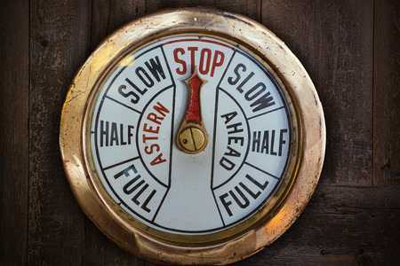 engine room: engine telegraph in front of an old wooden wall Stock Photo