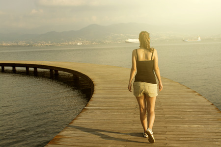lightness: Young woman in walking on a pier Stock Photo