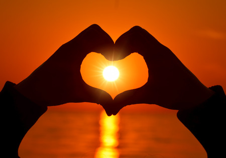 heart shapewith hands  on sunset photo
