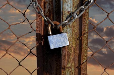 puertas de hierro: tecla de bloqueo con grilletes en valla oxidada Foto de archivo