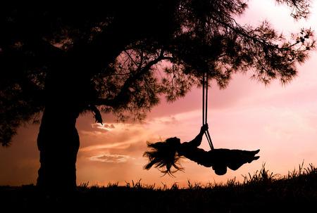 silhouet van gelukkige jonge vrouw op een schommel met een zonsondergang op de achtergrond