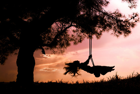 freedom girl: silhouette of happy young woman on a swing with sunset background