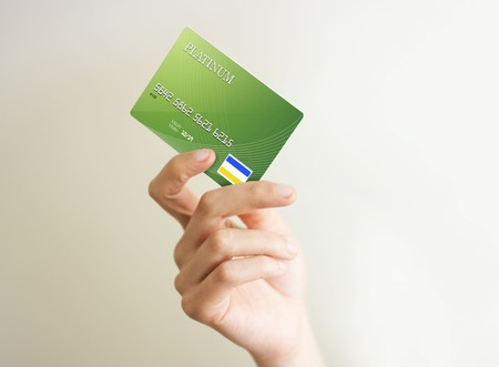 closeup of green credit card holded by hand.