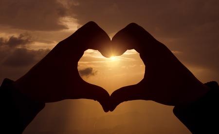 silhouette coeur: forme de coeur avec les mains sur le coucher du soleil Banque d'images
