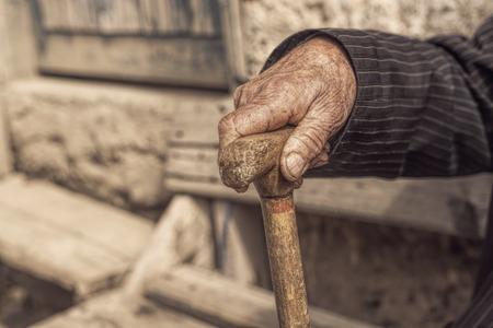 Hand eines alten Mannes hält einen Stock