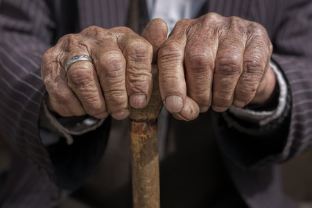 retirement age: hand of a old man holding a cane