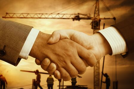 construction companies: business hand shake and a office in background