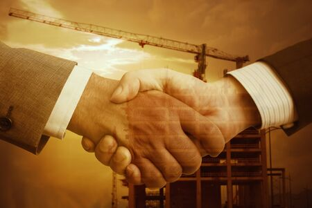 business relationship: Worker and architect shaking hands at construction site Stock Photo