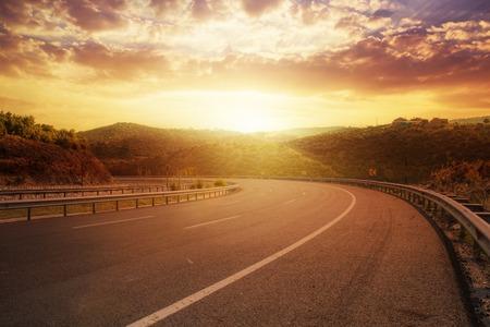 dramatic sunrise: fantastic sunset over asphalt road