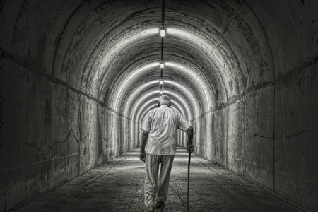 Old man goes alone through the tunnel