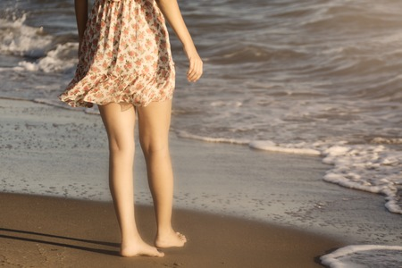 indentation: The legs of a woman walking on a beach