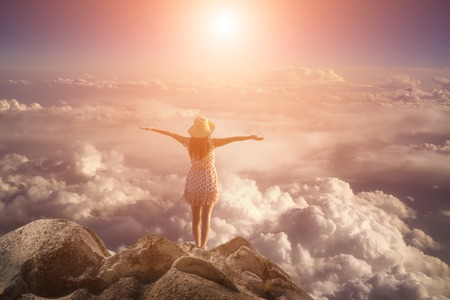 freedom young  woman jumping on mountain peak rock Stock Photo