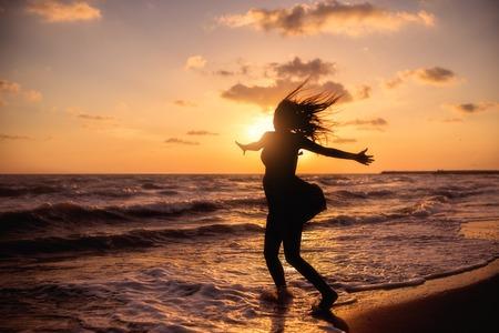 海の夕日にジャンプ幸せな女