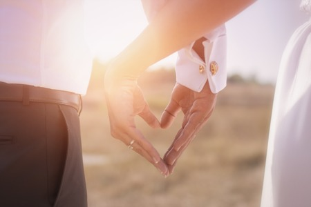 groom: Holding Hands with wedding rings on the background of sunlight Stock Photo