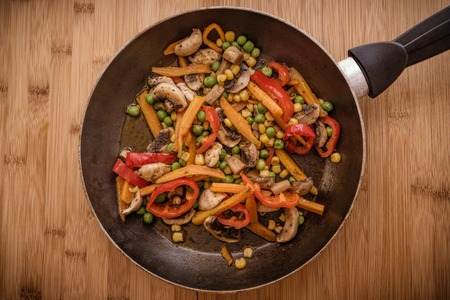 concoct: frypan and vegetables on wooden background