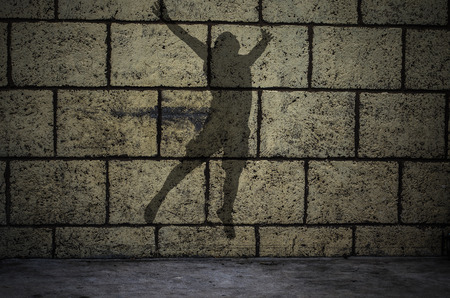 man silhouette  jumping in front of the brick wall