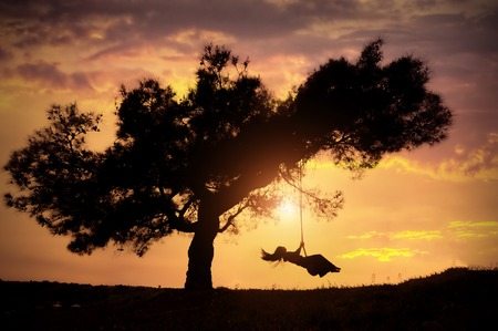 columpio: silhouette of happy young woman on a swing with sunset background