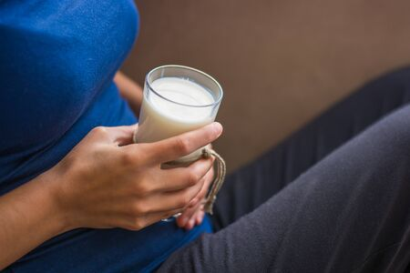 vaso de leche: Woman sitting and holding glass of milk on her bed