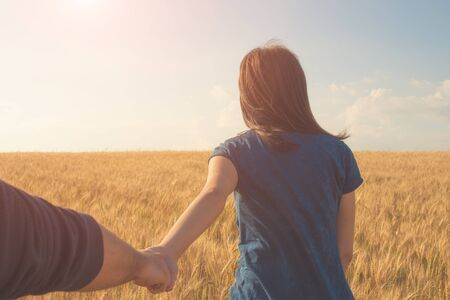 boyfriend: Young woman holding man hand on the wheat field Focus on hands. traveller, vintage processed.