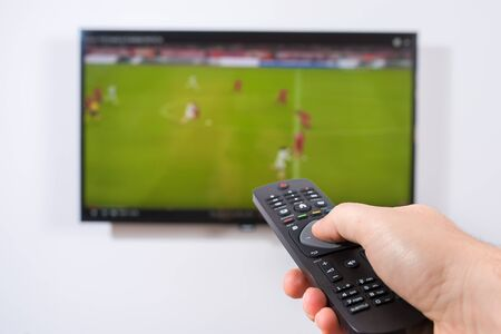 games hand: Watching soccer game on TV