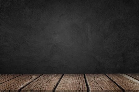 Sfondo con grunge muro nero e coperta tavolo di legno.