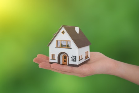 house in hands on Green Background