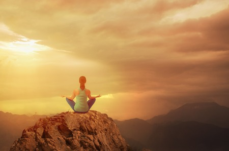 peace risk: Young woman sitting and meditating with crossed legs on mountain summit.