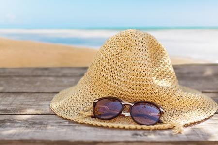 sombrero de fieltro y gafas de sol sobre la mesa de madera y fondo de paisaje del mar. la relajación o vacaciones concepto