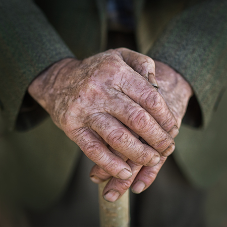 old hand: hands of a senior man on cane