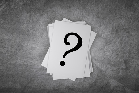 Paper card on a concrete table with question mark sign with free space