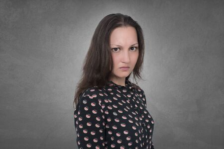 aggresive: Angry Woman expression on grey wall