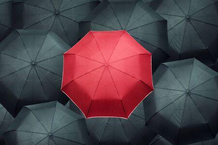 best shelter: Red different umbrella over many black umbrellas. Business leadership concept.