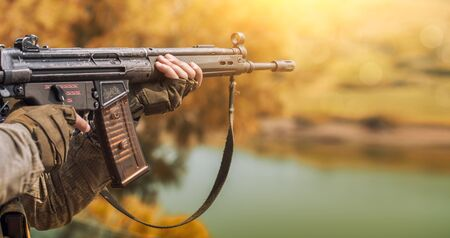 The soldier in camouflage and protective gloves, holding a gun. The zone of military operations. Stock Photo