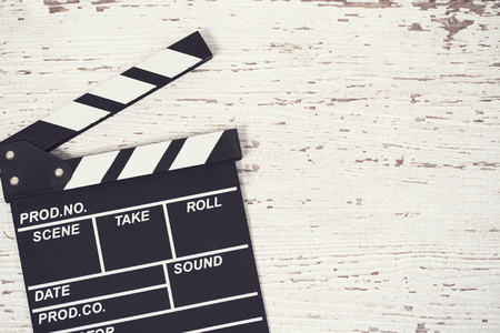 Screenwriter desktop with movie clapper board wooden background top view Stock Photo