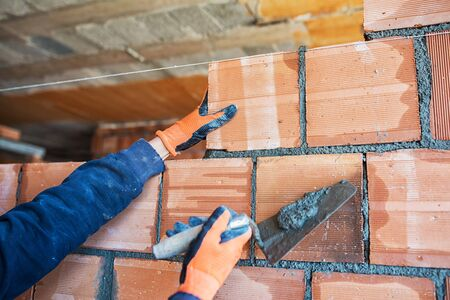 putty knives: Bricklayer worker installing brick masonry on exterior wall with trowel putty knife
