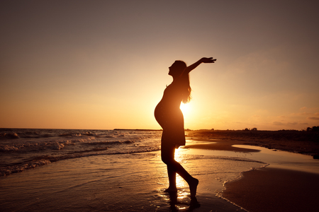 silhouette of a pregnant woman walking on the beach at sunset