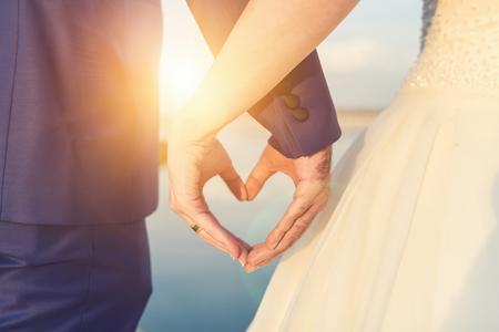 De holdingshanden van het huwelijkspaar op zonsondergangachtergrond