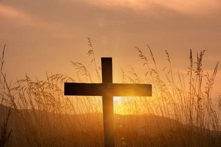 christian cross silhouette on sunset background Stock Photo