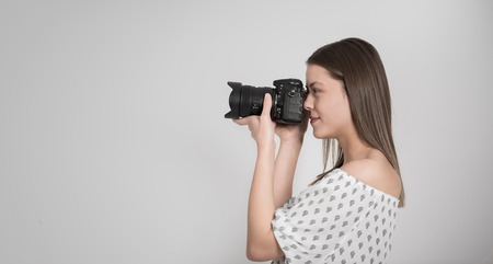 Woman photographer taking photograph against grey background