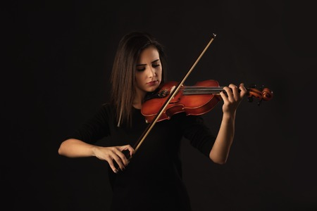 Beautiful Violinist Woman playing violin on black background