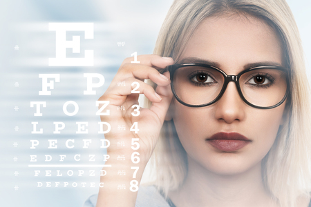 Young woman with spectacles on eyesight test chart background Stockfoto