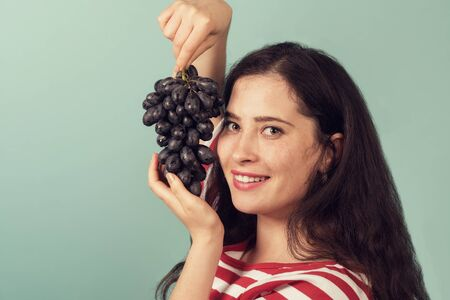 Smiling girl holding grapes near her face and smiling broadly to the viewer.