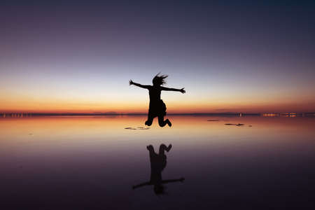 Woman jumping up in a beautiful sunset w,th reflection. Stock Photo