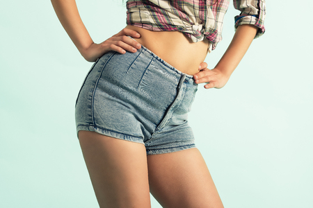 Beautiful woman body in denim jeans shorts on green background