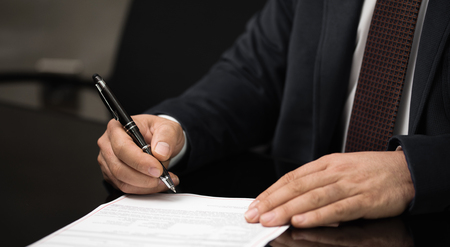 hand of a businessman signing or writing a document on a sheet of white paper using a nibbed fountain pen.