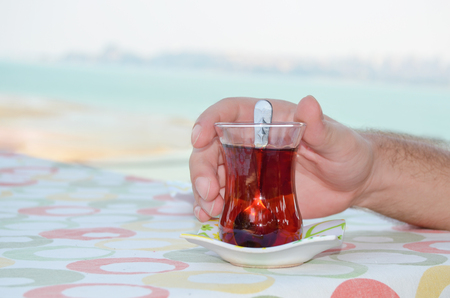 traditional Turkish tea and mans hand against the landsape.