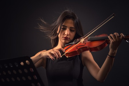 Pretty young woman playing a violin over black background.