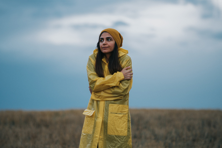 Young girl wearing a yellow raincoat in rainy and cold day