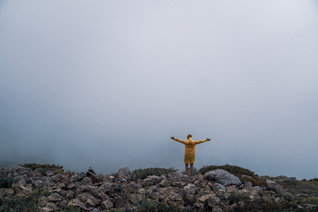 Female in yellow raincoat, jeans shorts standing at top of mountain with view of peaks at horizon. Landscape. Nature. Valley. Travel. Freedom. Vacation. Hills. Success. Contemplation. Flight